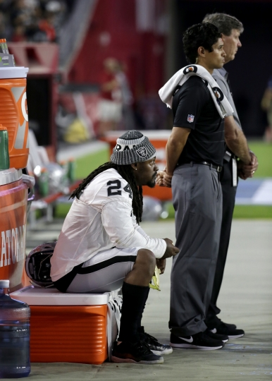 FILE - In this Aug. 12, 2017, file photo, Oakland Raiders running back Marshawn Lynch sits during the national anthem prior to the team's NFL preseason football game against the Arizona Cardinals in Glendale, Ariz. What started as a protest against police brutality has mushroomed a year later into a divisive debate over the future of former San Francisco 49ers quarterback Colin Kaepernick who refused to stand for the national anthem and now faces what his fans see as blackballing for speaking out in a country roiled by racial strife. Other prominent NFL players, such as Lynch, have sat out or demonstrated during anthems this preseason. (AP Photo/Rick Scuteri, File)