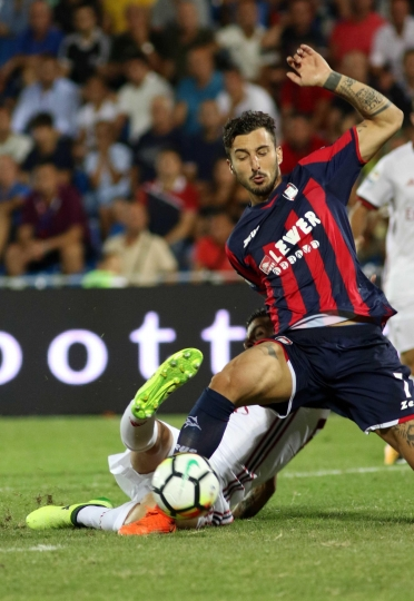 Crotone's Federico Ceccherini, right, fouls AC Milan's Patrick Cutrone in the penalty box during their Serie A soccer match at the Ezio Scida stadium in Crotone, Italy, Sunday, Aug. 20, 2017. (Albano Angilletta/ANSA via AP)