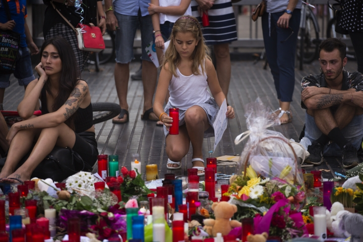 A girl places a candle after a terror attack that killed 14 people and wounded over 120 in Barcelona, Spain, Sunday, Aug. 20, 2017. (AP Photo/Emilio Morenatti)