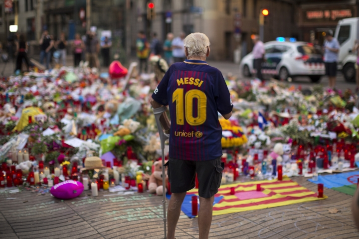 A man stands next to flags, flowers, messages and candles to the victims on Barcelona's historic Las Ramblas promenade on the Joan Miro mosaic, embedded in the pavement where the van stopped after killing at least 14 people in Barcelona, Spain, Monday, Aug. 21, 2017. (AP Photo/Emilio Morenatti)