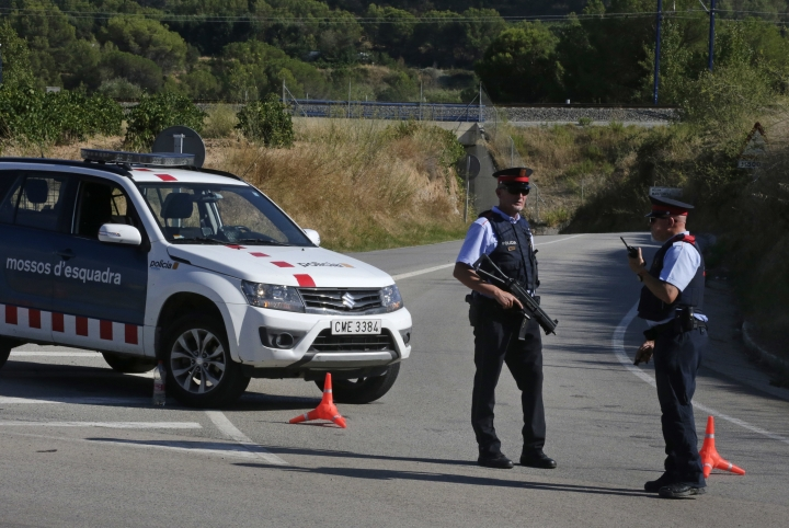 Armed police officers stand guard near Subirats, Spain, Monday, Aug. 21, 2017. A police operation was underway Monday in an area west of Barcelona, and a Spanish newspaper reports that the fugitive in the city's van attack has been captured. Regional police said officers shot a man wearing a possible explosives belt in Subirats, a small town 45 kilometers (28 miles) west of Barcelona. (AP Photo/Emilio Morenatti)