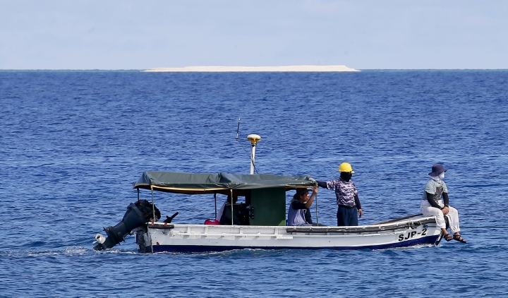 In this Friday, April 21, 2017 photo, engineers from NAMRIA, the central mapping agency of the Philippine Government, survey the area around the Philippine-claimed Thitu Island with a sandbar sitting on the horizon off the disputed South China Sea in western Philippines. On Tuesday, Aug. 22, 2017, two Filipino security officials said China has deployed its navy and coast guard ships in a cluster of uninhabited sandbars in the disputed South China Sea amid concerns that the Philippines may build structures on them in an emerging territorial issue that the government stated was quickly resolved. (AP Photo/Bullit Marquez)