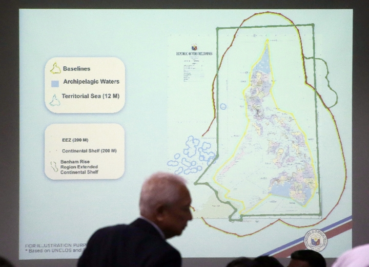 A man walks past a map of the Philippines and it's archipelagic waters during a budget meeting in Manila, Philippines on Tuesday, Aug. 22, 2017. Two Filipino security officials say China has deployed its navy and coast guard ships in a cluster of uninhabited sandbars in the disputed South China Sea amid concerns that the Philippines may build structures on them in an emerging territorial issue that the government stated was quickly resolved. The Chinese presence sparked concerns in Manila but Philippine Foreign Affairs Secretary Alan Peter Cayetano said without elaborating that the issue has been resolved. (AP Photo/Aaron Favila)