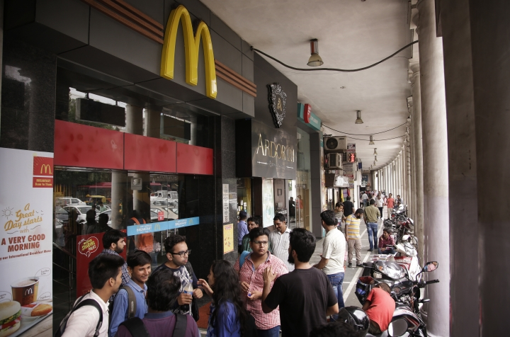 Indians stand at the entrance to a McDonald's outlet in New Delhi, India, Tuesday, Aug. 22, 2017. McDonald's India has announced it will close nearly 170 McDonald's outlets in northern and eastern India after the American fast food giant decided to terminate a franchise agreement with its Indian partner. (AP Photo/Altaf Qadri)