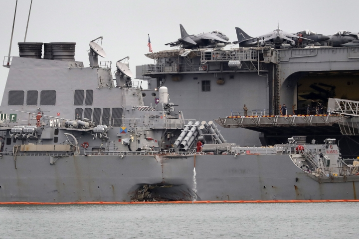 The damaged port aft hull of USS John S. McCain, left, is seen while docked next to USS America at Singapore's Changi naval base on Tuesday, Aug. 22, 2017 in Singapore. The focus of the search for 10 U.S. sailors missing after a collision between the USS John S. McCain and an oil tanker in Southeast Asian waters shifted Tuesday to the damaged destroyer's flooded compartments. (AP Photo/Wong Maye-E)