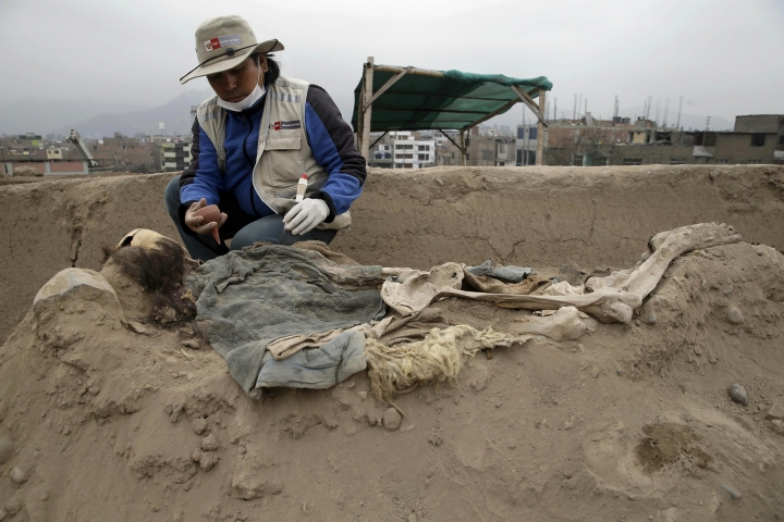 An archeologist works at the site where 16 tombs belonging to 19th century Chinese immigrants were discovered, at Huaca Bellavista in Lima, Peru, Thursday, Aug. 24, 2107. According to the Ministry of Culture of Peru, the tombs where located in a pre-Inca sacred site because Chinese immigrants could not be buried in the Catholic cemeteries of the time. (AP Photo/Martin Mejia)