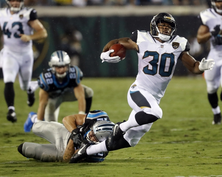 Jacksonville Jaguars running back Corey Grant (30) is tripped up by Carolina Panthers safety Colin Jones after running for more than 50 yards on a fake punt during the first half of an NFL preseason football game, Thursday, Aug. 24, 2017, in Jacksonville, Fla. (AP Photo/Stephen B. Morton)