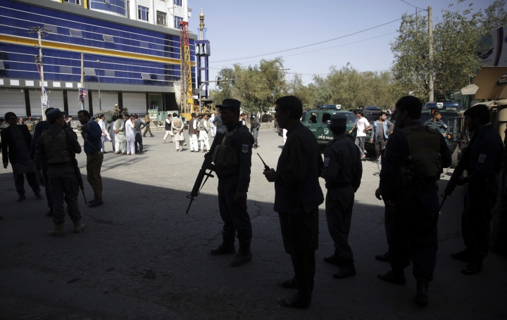 Security forces and civilians walk near a Shiite mosque during an ongoing attack, Kabul, Afghanistan, Friday, Aug. 25, 2017. Gunmen stormed a Shiite mosque in the Afghan capital while worshippers were at Friday prayers, setting off an explosion that killed a security guard outside and pushing into the shrine, officials said. (AP Photo/Massoud Hossaini)