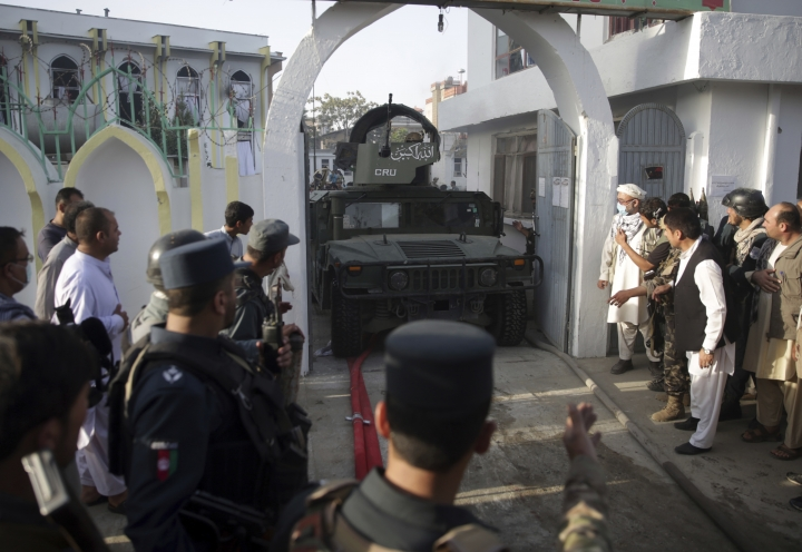 A military vehicle exits after an attack on a Shiite mosque in Kabul, Afghanistan, Friday, Aug. 25, 2017. A senior hospital official says at least 20 people were killed in the hours-long siege of a Shiite Muslim mosque in the Afghan capital of Kabul. (AP Photo/Massoud Hossaini)