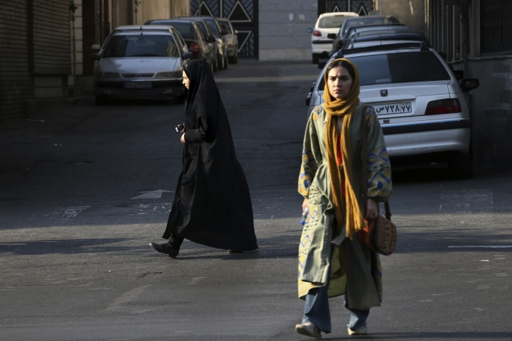 In this Thursday, Aug. 24, 2017, photo, two Iranian women make their way in a square while one of them wears the chador in downtown Tehran, Iran. She is just a couple of weeks into her appointment as new Iranian vice president but Laaya Joneidi's decision to abandon her headscarf and fashion style for the all-encompassing black chador is raising questions among women in the Islamic Republic _ especially after she said that President Hassan Rouhani personally asked her to wear the more conservative Muslim women's garment. (AP Photo/Vahid Salemi)