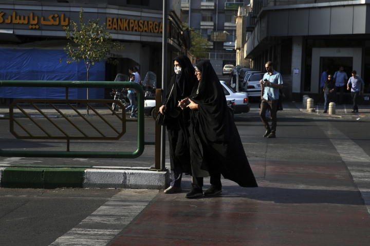 Two Iranian women cross a street while wearing the chador, a head-to-toe garment, in downtown Tehran, Iran. She is just a couple of weeks into her appointment as new Iranian vice president but Laaya Joneidi's decision to abandon her headscarf and fashion style for the all-encompassing black chador is raising questions among women in the Islamic Republic _ especially after she said that President Hassan Rouhani personally asked her to wear the more conservative Muslim women's garment. (AP Photo/Vahid Salemi)