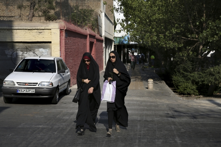 "In this Thursday, Aug. 24, 2017, photo, two Iranian women cross a street while wearing the ""chador,"" a head-to-toe garment, in downtown Tehran, Iran. She is just a couple of weeks into her appointment as new Iranian vice president but Laaya Joneidi's decision to abandon her headscarf and fashion style for the all-encompassing black chador is raising questions among women in the Islamic Republic _ especially after she said that President Hassan Rouhani personally asked her to wear the more conservative Muslim women's garment. (AP Photo/Vahid Salemi)"