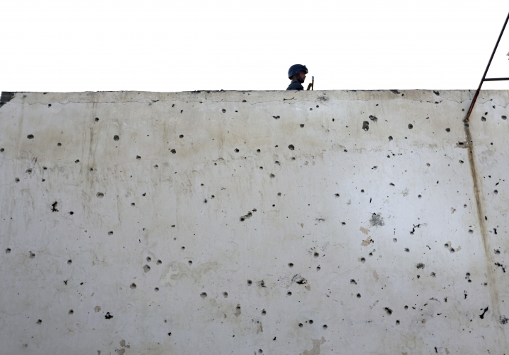 An Afghan police officer stands guard on a bullet ridden wall at a Shiite mosque where gunmen attacked during Friday prayers, in Kabul, Afghanistan, Saturday, Aug. 26, 2017. Militants stormed the packed Shiite mosque during Friday prayers in an attack killing worshippers, an official said. (AP Photo/Rahmat Gul)