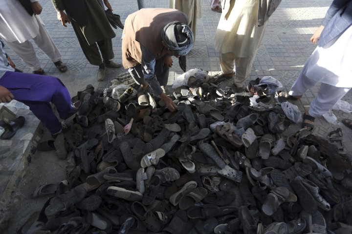Afghan men search shoes of their relatives inside a Shiite mosque where gunmen attacked during Friday prayers, in Kabul, Afghanistan, Saturday, Aug. 26, 2017. Militants stormed the packed Shiite mosque during Friday prayers in an attack killing worshippers, an official said. (AP Photo/Rahmat Gul)