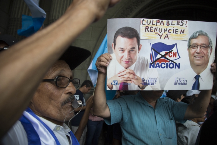 """A demonstrator holds images of Guatemala's President Jimmy Morales, left, and his Vice President Jafeth Cabrera that reads in English: """"Guilty! Resign now!"""" during a protest outside the National Palace of Culture in Guatemala City, Sunday, Aug. 27, 2017, as Morales stands firm on his decision to expel the head of a U.N. anti-corruption commission. On Friday, the U.N. commission announced they were seeking the removal of Morales' immunity to pursue an investigation into campaign finance violations. (AP Photo/Luis Soto)"""