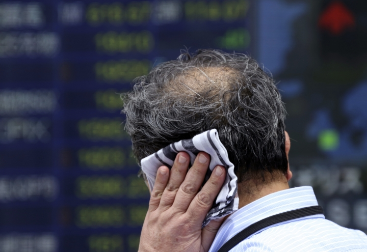 A man wipes the sweat from his head while he looks at an electronic stock board of a securities firm in Tokyo, Monday, Aug. 28, 2017. Asian stocks were mixed Monday after investors found no surprises from last week's key meeting of central bankers while gasoline futures spiked after Tropical Storm Harvey battered Texas' refinery-rich Gulf Coast.(AP Photo/Koji Sasahara)