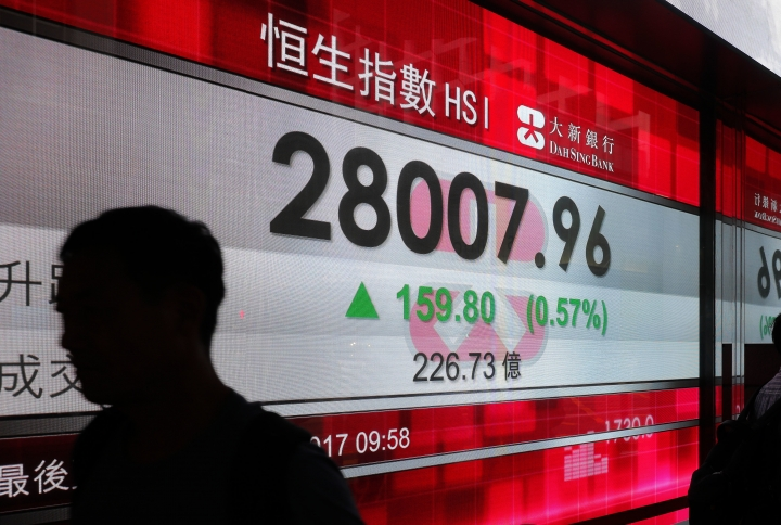 A man walks past an electronic board showing Hong Kong share index outside a local bank in Hong Kong, Monday, Aug. 28, 2017. Asian stocks were mixed Monday after investors found no surprises from last week's key meeting of central bankers while gasoline futures spiked after Tropical Storm Harvey battered Texas' refinery-rich Gulf Coast. (AP Photo/Vincent Yu)