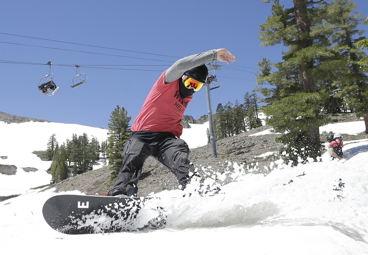 FILE - In this July 1, 2017 file photo, a snow boarder cuts throughout the snow at the Squaw Valley Ski Resort in Squaw Valley, Calif. A ski resort at Lake Tahoe has announced a new partnership with a leading outdoor retailer in China to try to help attract more Chinese skiers and snowboarders to the region. The agreement between Squaw Valley Alpine Meadows and Toread builds on the Sierra resort's existing alliance with China's Genting Resort Secret Garden. (AP Photo/Rich Pedroncelli, File)