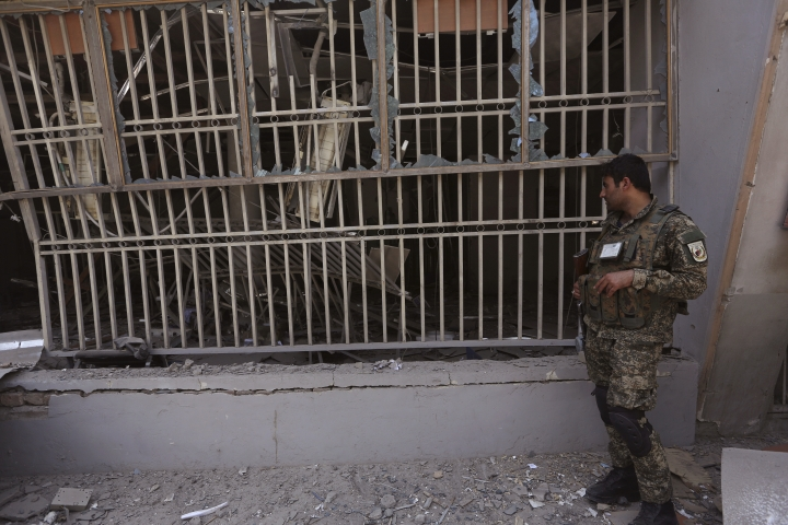 An Afghan security guard stands in front of a bank after suicide bombing in Kabul, Afghanistan, Tuesday, Aug. 29, 2017. A suicide bombing on Tuesday in a busy commercial area in Kabul, near a string of banks and not far from the U.S. Embassy, killed several people, Afghan officials said. (AP Photo/Rahmat Gul)
