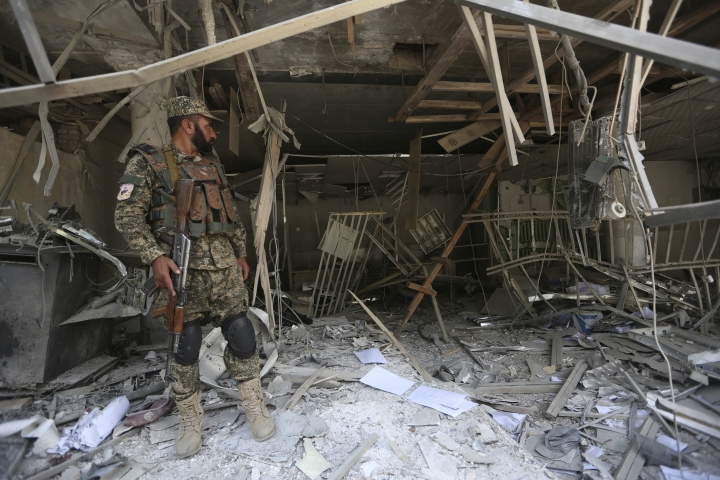 Afghan security guard stands inside a bank after suicide bombing in Kabul, Afghanistan, Tuesday, Aug. 29, 2017. A suicide bombing on Tuesday in a busy commercial area in Kabul, near a string of banks and not far from the U.S. Embassy, killed several people, Afghan officials said. (AP Photo/Rahmat Gul)