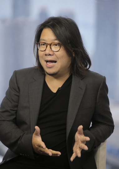 """In this Friday, Aug. 25, 2017, photo, Singaporean novelist Kevin Kwan gestures during an interview in Hong Kong. Kwan was in Hong Kong promoting the third and last book in his 'Crazy Rich' trilogy – 'Rich People Problems.' His first book """"Crazy Rich Asians"""" released in 2013, rose quickly in the charts and became a best seller. (AP Photo/Vincent Yu)"""