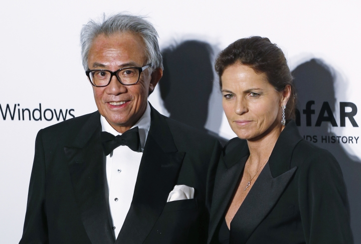 In this Saturday, March 14, 2015, photo, Hong Kong businessman and socialite David Tang, left, poses with his wife Lucy on the red carpet for the fundraising gala organized by amfAR (The Foundation for AIDS Research) in Hong Kong. Tang, a flamboyant and outspoken socialite and entrepreneur who founded the Shanghai Tang fashion brand, has died. He was 63. (AP Photo/Kin Cheung)