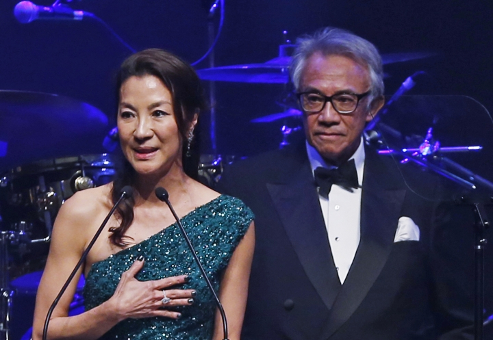 In this Saturday, March 14, 2015, photo, Hong Kong businessman and socialite David Tang, right, and Malaysian actress Michelle Yeoh attend the fundraising gala organized by amfAR (The Foundation for AIDS Research) in Hong Kong. Tang, a flamboyant and outspoken socialite and entrepreneur who founded the Shanghai Tang fashion brand, has died. He was 63. (AP Photo/Kin Cheung)