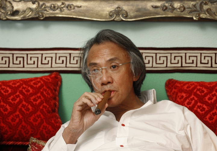 In this March 20, 2007, file photo, Hong Kong businessman David Tang smokes cigar during an interview at his home in Hong Kong. Tang, a flamboyant and outspoken socialite and entrepreneur who founded the Shanghai Tang fashion brand, has died. He was 63. (AP Photo/Vincent Yu)