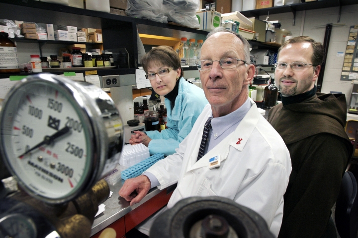 FILE - In this Feb. 5, 2009 file photo, University of Massachusetts professor Dr. James Dobson, Jr., center, posses with his wife Susan, left, and Teresian Carmelite Prior Dennis-Anthony Wyrzykowski, right, in Dobson's laboratory at the University of Massachusetts Medical School in Worcester, Mass. Wyrzykowski's monastery teamed with Dobson to sell Easeamine, a face cream containing a patented substance the scientist found while studying other anti-aging compounds in the heart. In August 2017, Wyrzykowski, his company and UMass filed a lawsuit against cosmetics giant L'Oreal, accusing the company of stealing patented technology used in the cream that his charity was selling to raise money for the poor. (AP Photo/Steven Senne, File)