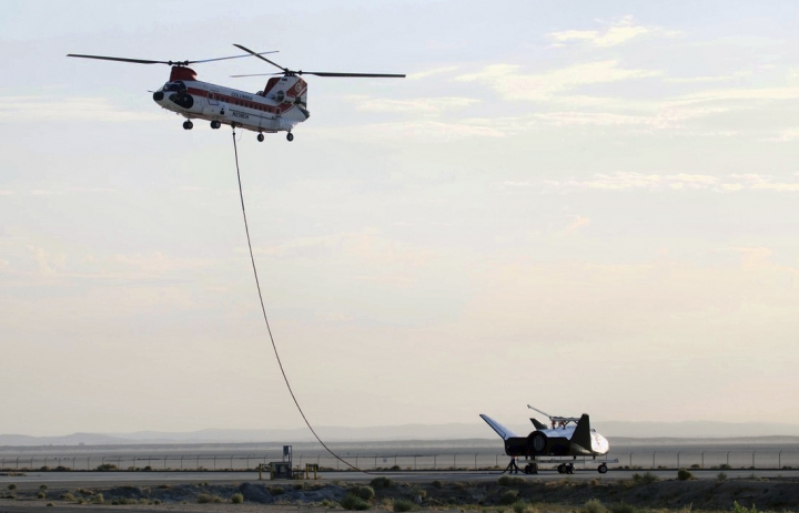"Sierra Nevada Corp's ""Dream Chaser"" test spacecraft is prepared to be lifted by a helicopter for a test at Edwards Air Force Base, Calif. on Wednesday, Aug. 30, 2017. The test version of a spacecraft resembling a mini space shuttle was carried aloft over the Mojave Desert by a helicopter in a precursor to a free flight in which it will be released to autonomously land on a runway as it would in an actual return from orbit. Sierra Nevada Corp.'s Dream Chaser craft was lifted off the ground at NASA's Armstrong Flight Research Center on Edwards Air Force Base and was carried to the same altitude and flight conditions it will experience before release in a free flight. (Matt Hartman via AP)"