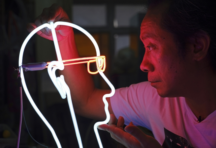 In this Aug. 15, 2017, photo, Wu Chi-kai, one of about half a dozen active neon sign masters left in Hong Kong, looks at his work during an interview in Hong Kong. For Hong Kong's famed neon lights, the future looks dim. Neon-lit signs were once ubiquitous here, illuminating city streets with their soft, warm glow and giving the dynamic Asian city a signature look to match its postwar economic boom. (AP Photo/Vincent Yu)