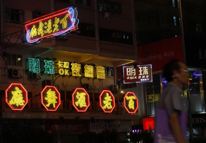 In this Aug. 21, 2017, photo, a man walks past some neon signs at a down town street in Hong Kong. For Hong Kong's famed neon lights, the future looks dim. Neon-lit signs were once ubiquitous here, illuminating city streets with their soft, warm glow and giving the dynamic Asian city a signature look to match its postwar economic boom. (AP Photo/Vincent Yu)