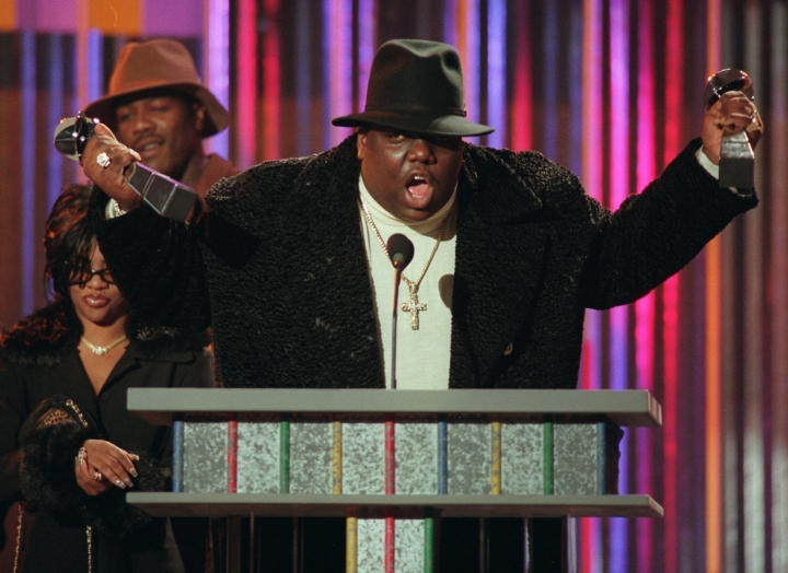 """FILE - In this Dec. 6, 1995, file photo, rapper Notorious B.I.G., who won rap artist and rap single of the year, clutches his awards at the podium during the annual Billboard Music Awards in New York. Voletta Wallace details the love for the Notorious B.I.G. as both his mother and No. 1 fan in the new, three-hour documentary, """"Biggie: The Life of Notorious B.I.G."""" It debuts Monday, Sept. 4, 2017, at 8 p.m. EST on A&E. (AP Photo/Mark Lennihan, File)"""