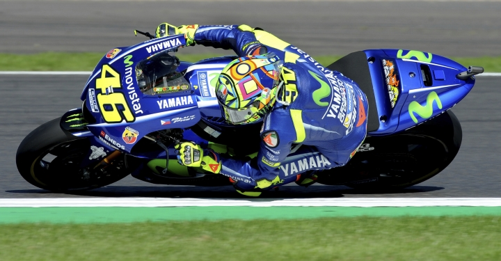 FILE -- In this Aug. 27, 2017 file photo, Italy's Valentino Rossi of Movistar Yamaha steers his bike during the Moto GP race at the British Grand Prix at Silverstone, England. Six-time MotoGP champion Rossi has reportedly broken his right leg in a training accident in Italy. According to Italian sports daily Gazzetta dello Sport, Rossi fell during enduro training and fractured his tibia and fibula. (AP Photo/Rui Vieira)