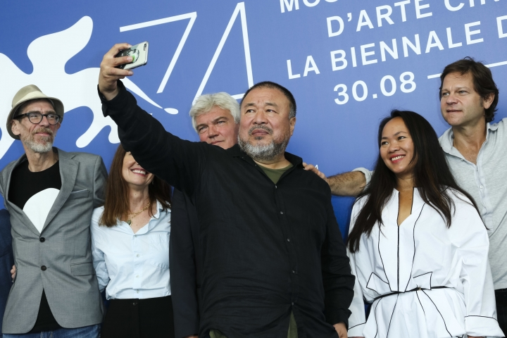 """Artist Ai Weiwei, center, snaps selfie photographs during the photo call for the film """"Human Flow"""" at the 74th Venice Film Festival at the Venice Lido, Italy, Friday, Sept. 1, 2017. (Photo by Joel Ryan/Invision/AP)"""