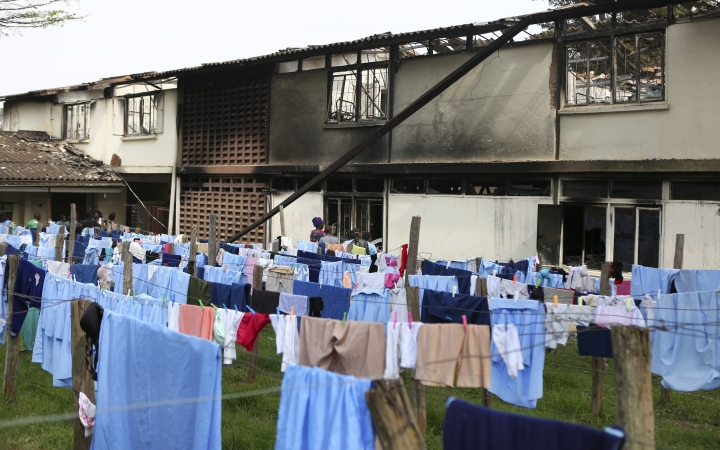 Parents observe the burned dormitory in front of the students' laundry hanging on washing lines, following a fire at the Moi Girls High School in Nairobi, Kenya, Saturday, Sept. 2, 2017. Seven girls died early Saturday when a fire gutted their dormitory at the high school in Kenya's capital, the country's education minister said. (AP Photo/Brian Inganga)