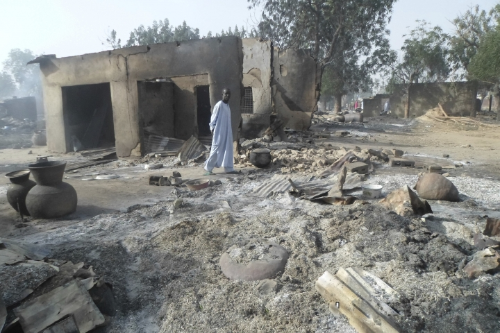 FILE - In this Sunday Jan. 31, 2016 file photo, a man walks past burnt out houses following an attacked by Boko Haram in Dalori village near Maiduguri. Nigeria-based Boko Haram extremists have killed more than 380 people in the Lake Chad region since April, a major resurgence of attacks that has resulted in double the casualties compared to the five months before April, Amnesty International said Tuesday, Sept. 5, 2017. (AP Photo/Jossy Ola, File)