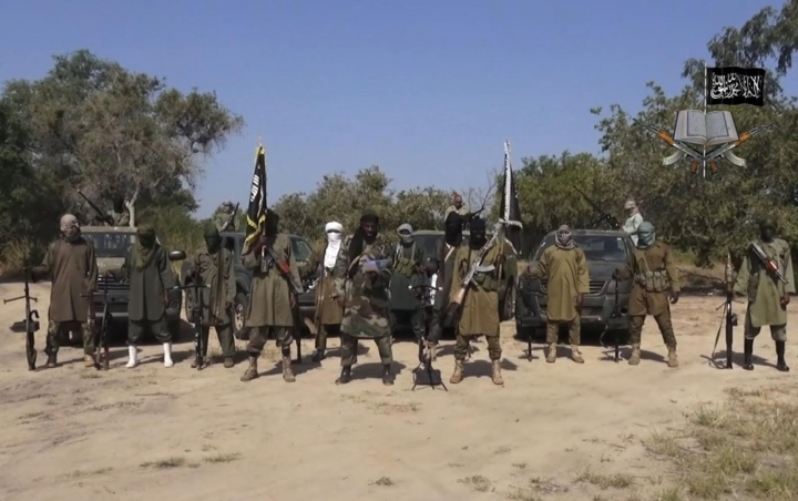 FILE - In this file image taken from video released Friday Oct. 31, 2014, by Boko Haram, Abubakar Shekau, centre, the leader of Nigeria's Islamic extremist group, surrounded by his fighters. Nigeria-based Boko Haram extremists have killed more than 380 people in the Lake Chad region since April, a major resurgence of attacks that has resulted in double the casualties compared to the five months before April, Amnesty International said Tuesday, Sept. 5, 2017. (AP Photo/Boko Haram,File)