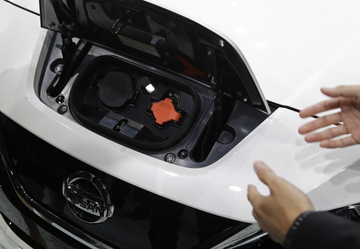 People look at the charging port on a 2018 Nissan Leaf during an unveiling event, Tuesday, Sept. 5, 2017, in Las Vegas. Japanese automaker Nissan Motor Co. unveiled its zero-emissions vehicle in the U.S. late Tuesday. (AP Photo/John Locher)