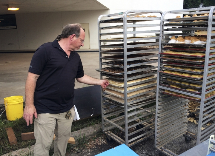 In this Sept. 2, 2017 photo, Bobby Jucker, owner of Three Brothers Bakery, cleans up the storm damage at his bakery in Houston. In 2008, Hurricane Ike tore the roof off his business. Now he estimates he's facing $1 million in damage and lost revenue from Hurricane Harvey, the fifth time a storm has put his bakery out commission. A week after Harvey dropped four feet of rain on Houston, America's fourth-biggest city is struggling to reopen for business. (AP Photo/Brian Melley)