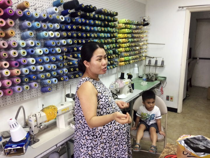 """In this Sept. 2, 2017 photo, Maria Tran, co-owners of Chic Tailors, near Brays Bayou in Meyerland, Texas, prepares to open her business with her 3-year-old son, Ander. Tran wants to get the shop open quickly so her sister can take over while she gives birth to her second child, a daughter. She worries because she watched customers move away after previous floods. But for now she says she has """"no complaints. Compared with other people, we're lucky we're still here and alive.'' (AP Photo/Brian Melley)"""