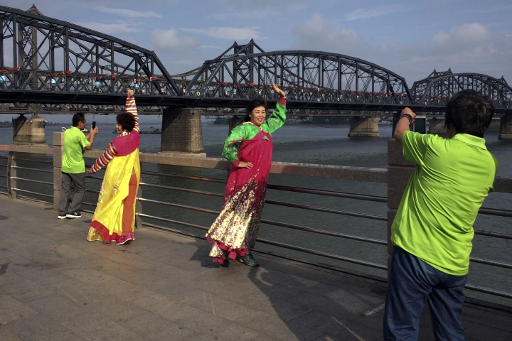 In this Tuesday, Sept. 5, 2017 photo, Chinese tourists in North Korean costumes pose for souvenir photos near the Friendship Bridge connecting China and North Korea in the Chinese border town of Dandong, opposite side of the North Korean town of Sinuiju. Rising international tensions over Pyongyang's missile launches and nuclear tests seem a distant concern in the Chinese border city of Dandong, where trucks rumble across the bridge to North Korea and people stroll the promenade beside the Yalu River within sight of North Korean border guards. (AP Photo/Helene Franchineau)