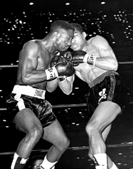 FILE - In this March 21, 1963, file photo, defending featherweight champion Davey Moore, left, trades punches with Sugar Ramos during first round of a scheduled 15-round fight in Los Angeles. Ramos, the Cuban featherweight champion whose fists led to two deaths in the ring, has died in Mexico City. He was 75. The World Boxing Council said he died Sunday, Sept. 3, 2017, of cancer. (AP Photo/File)