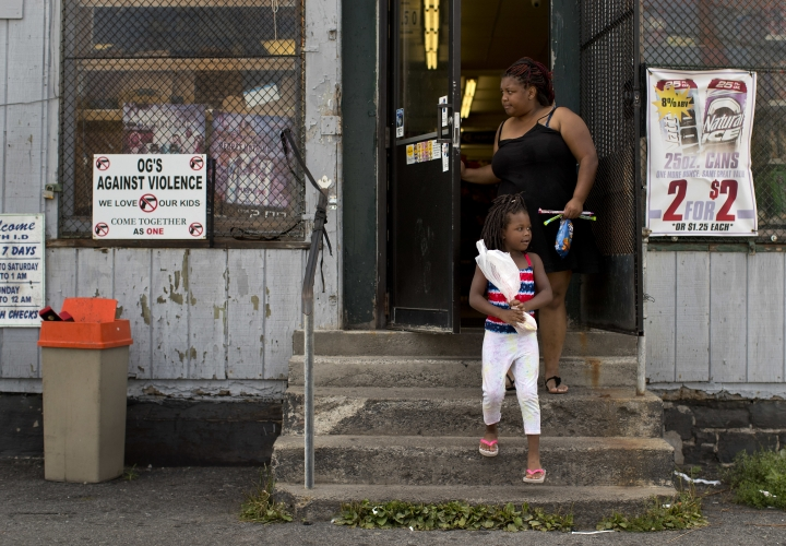 An anti violence sign, created by former gangsters hangs on a window of a corner convenience store where woman and her daughter finished shopping, Monday, Aug. 21, 2017, in the South Side neighborhood of Syracuse, N.Y. Syracuse is a modestly sized city with a big problem. Teenagers are being killed or injured by guns at a rate far higher than most other cities. (AP Photo/Julie Jacobson)