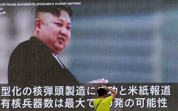 FILE - In this Aug. 6, 2017, file photo, a man takes a photo of a TV news program in Tokyo, showing an image of North Korean leader Kim Jong Un. U.N. experts say North Korea illegally exported coal, iron and other commodities worth at least $270 million to China and other countries including India, Malaysia and Sri Lanka during the six-month period ending in August in violation of U.N. sanctions. (AP Photo/Shizuo Kambayashi, File)