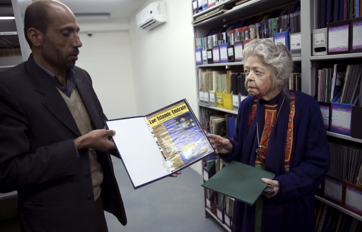 FILE - In this Tuesday, Dec. 9, 2014 file photo, American historian Nancy Hatch Dupree, right, and her colleague show an archived paper of the Taliban regime during an interview with The Associated Press at the Afghanistan Center in Kabul University. Dupree, who spent decades in Afghanistan working to preserve the heritage of the war-torn country has died following a long illness. An Afghan government statement said Sunday, Sept. 10, 2017, that Dupree, who first came to Afghanistan in 1962 and spent much of her life collecting and documenting historical artifacts, died in Kabul overnight at the age of 90(AP Photo/Massoud Hossaini, File)