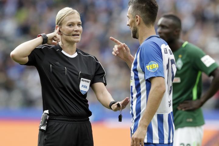 Referee Bibiana Steinhaus, left, speaks to a player during the German Bundesliga soccer match between Hertha BSC Berlin and SV Werder Bremen in Berlin, Germany, Sunday, Sept. 10, 2017. (AP Photo/Michael Sohn)