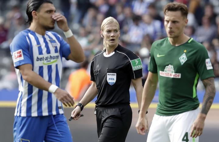 Referee Bibiana Steinhaus, center, speaks during the German Bundesliga soccer match between Hertha BSC Berlin and SV Werder Bremen in Berlin, Germany, Sunday, Sept. 10, 2017. (AP Photo/Michael Sohn)