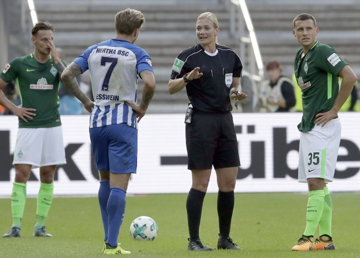 Referee Bibiana Steinhaus, 2nd right, talks to players during the German Bundesliga soccer match between Hertha BSC Berlin and SV Werder Bremen in Berlin, Germany, Sunday, Sept. 10, 2017. (AP Photo/Michael Sohn)