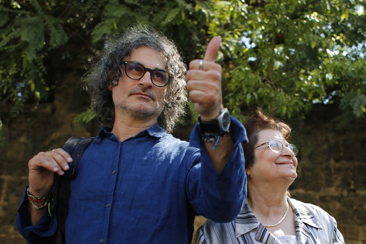 Lebanese film director Ziad Doueiri, left, gives a thump up next to his mother, Wafiqa, as he speaks to journalists after being released by a military court, in Beirut, Lebanon, Monday, Sept. 11, 2017. Doueiri was briefly detained upon arrival in Lebanon Sunday over previous visits to Israel and is undergoing further questioning on Monday, his ex-wife and Lebanese officials said. (AP Photo/Hassan Ammar)